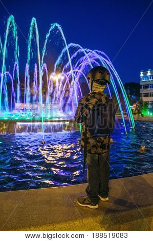 Small kid play with colorful fountain at Lima park.