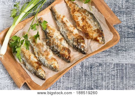 Roasted river fish roach on an old brown wooden tray.