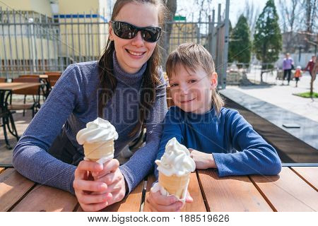 Cute little boy and his mother eating ice-cream in an outdoor cafe.
