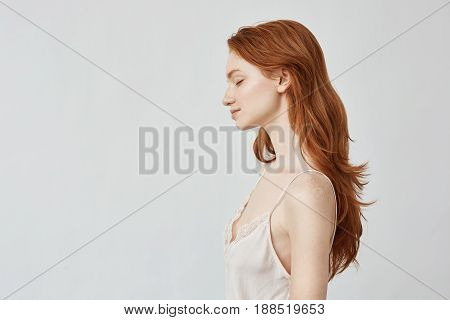 Portrait of young beautiful redhead girl in profile with closed eyes smiling. Copy space. Isolated on white background.
