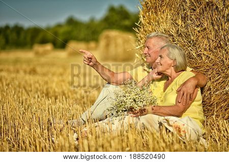 Senior couple sitting near stack of hay on moved field of wheat