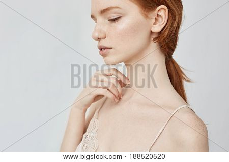 Close up portrait of tender young redhead girl posing over white background. Copy space. Isolated on white background.