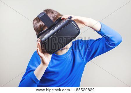 Teen boy wearing virtual reality VR glasses watching movies or playing video games