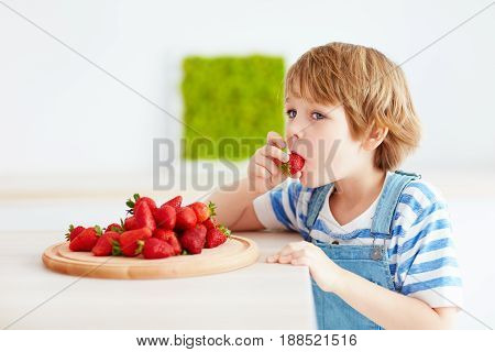 Cute Happy Kid Eating Tasty Ripe Strawberries On The Kitchen