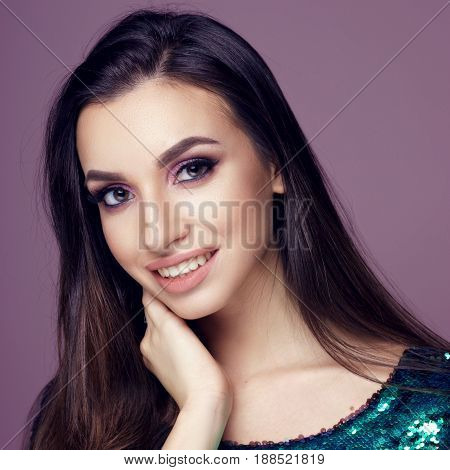 Closeup beauty studio fashion portrait of young smiling woman with long brunette dark hair and nakeup posing in shiny green dress with sequins posing against purple background and looking in camera.