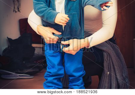 Parenting taking care of child concept. Mother dressing up her son in winter clothes before going out