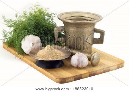 Still Life Spices, Ginger, marigold staminas in a copper vase on a wooden board on a background of a stern stupa for grinding spices, bunches of dill and garlic