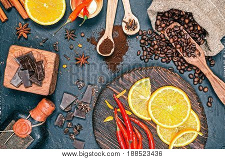 Roasted coffee beans, aroma spices, red chili peppers and orange fruit slices on black slate background. Close-up top view