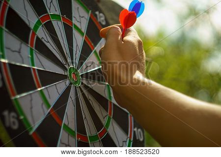 outdoor darts game with man hand and blurry green background