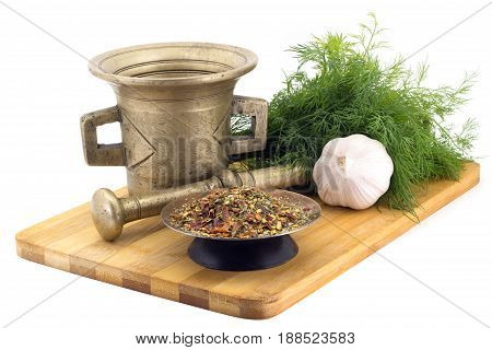 Still Life Spices, Mix of hot peppers , marigold staminas in a copper vase on a wooden board on a background of a stern stupa for grinding spices, bunches of dill and garlic
