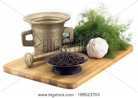 Still Life Spices, tellicherry pepper , marigold staminas in a copper vase on a wooden board on a background of a stern stupa for grinding spices, bunches of dill and garlic