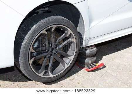 car in repair at the mechanic has a punctured tire