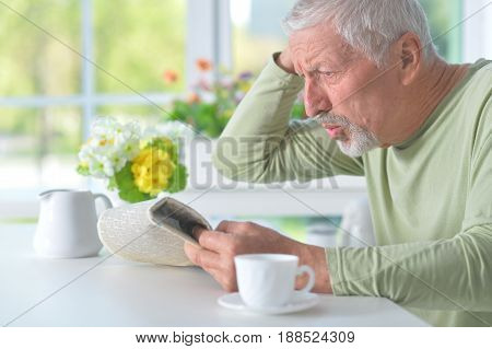Beautiful old man reading a newspaper at a table
