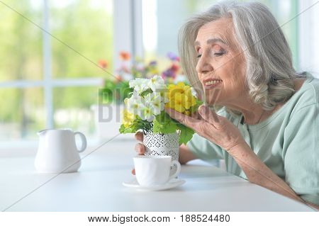 Beautiful old woman with flowers at the table