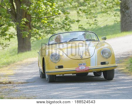 STOCKHOLM SWEDEN - MAY 22 2017: Yellow Porche Sportster classic car from 1958 driving on a country road in the public race Gardesloppet in the forests at Djurgarden Stockholm Sweden. May 22 2017