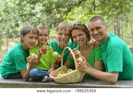 Big happy family near wooden table with basket full of apples