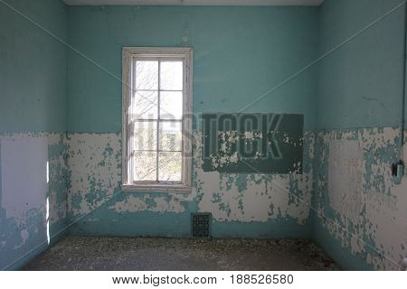 A window in a room of an old abandoned asylum