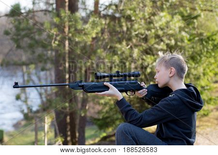 young teenager with air gun in forest