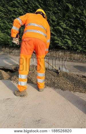 Man At Work With High Visibility Orange Clothing And Yellow Helm