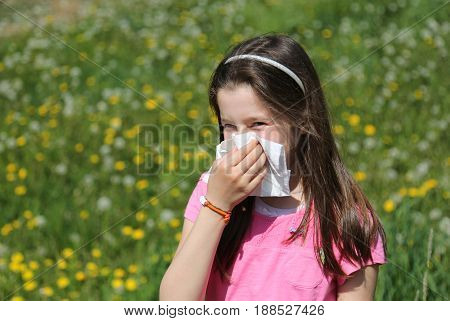 Child with brown hair with allergy to the grasses blows her nose with the handkerchief in the middle of the meadow in spring