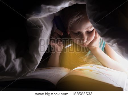 Children bedtime. Sister are reading a book under a blanket with flashlight. Pretty young girl having fun in children room.