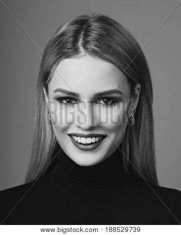 The face of beauty. Woman with long straight blonde hair, cherry lips and colorful eye shadow. Happy joyous smiling woman