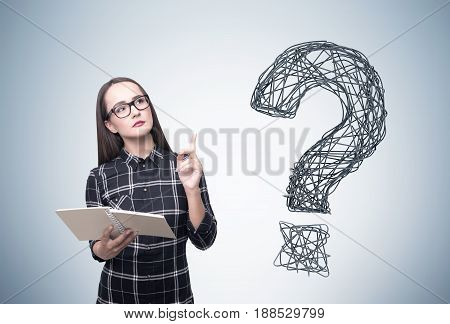 Geek young woman wearing a checkered shirt is holding a book and standing near a gray wall with a wire question mark near her.