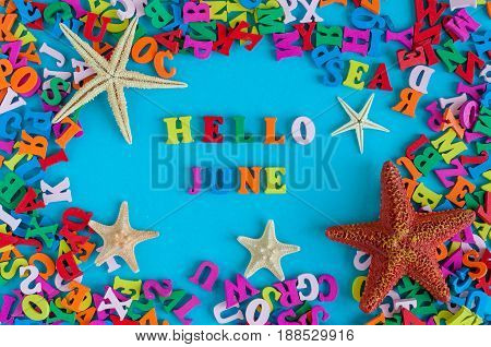 Hello June - word composed of small colored letters at blue background with beach attribute - starfish or five-finger. Summerbeginning and vacation concept.
