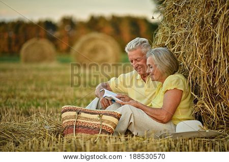 Happy senior couple on mowed field of wheat with hay