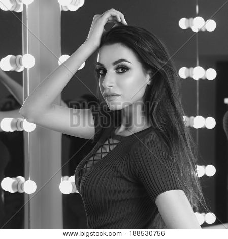 Young sexy girl in blue elegant dress standing and posing in interior with mirrors and lightning bulbs. Fashion model with long brunette hair and makeup