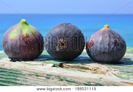 Three blue figs on green grunge wooden background against blue sea bokeh
