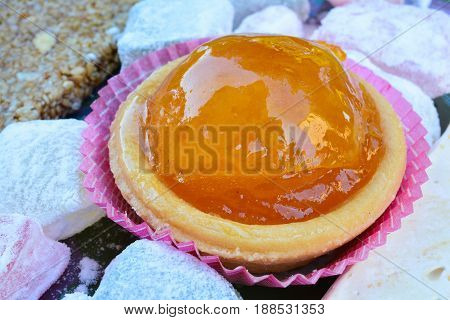 Candied orange in punnet of dough served with Turkish delight and and halva close up view