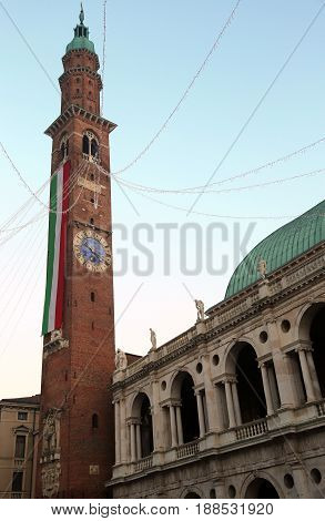 High Bell Tower With Enormous Italian Flag Of The Historic Building Of The Main Square Of Vicenza Ci
