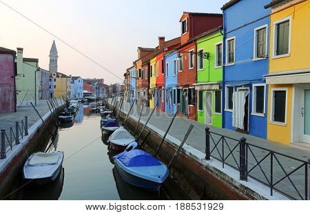 Boats Moored In The Waterway Near The Colorful Houses Of The Island Of Burano In Italy