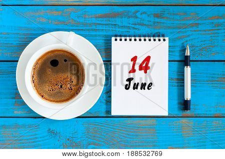 June 14th. Image of june 14 , daily calendar on blue background with morning coffee cup. Summer day, Top view.