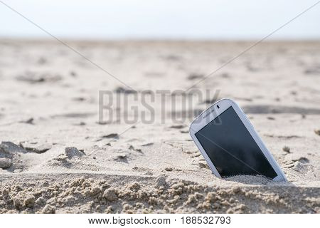 Mobile touch phone in sand on a beach.