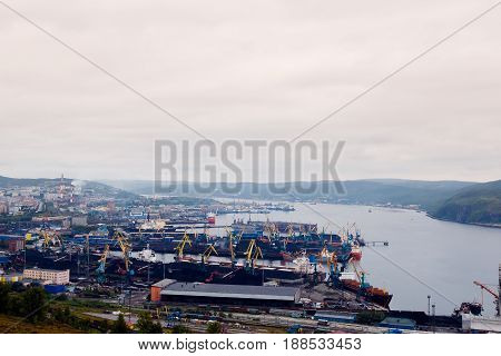 Embankment along with the river port, the crane unloads the coal from the box and loads it into the truck. Murmansk, Russia.Concept logistics, transportation, transport.
