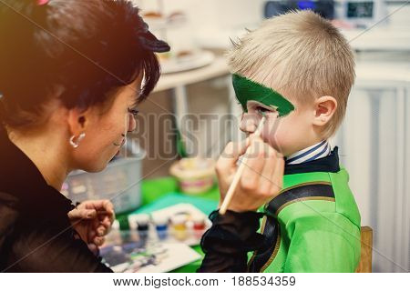 woman painting face of kid outdoors. baby face painting