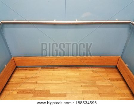 inside blue elevator with wooden floor and metal railing