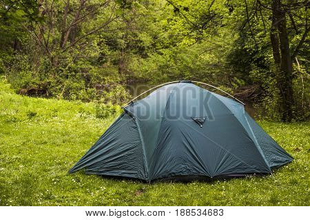 green tourist tent in the forest near the river