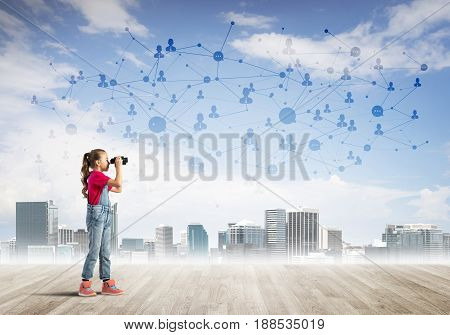 Cute kid girl standing on wooden floor and looking in binoculars
