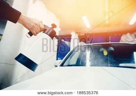 Car wash worker close-up removes stains on the car. Concept of washing a modern car with high-pressure water.Toning and highlighting.