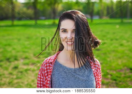 Portrait of beautiful model girl in the park. Looking at camera. Positive human emotion facial expression body language, concept of funny hipster girl