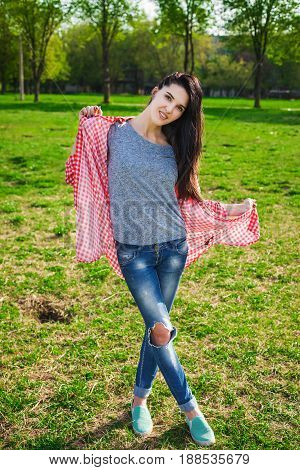 beautiful hipster woman in the park. Looking at camera. Positive human emotion facial expression body language, concept of funny girl. Dressed in a gray shirt, blue jeans and a Tshirt in a red cage