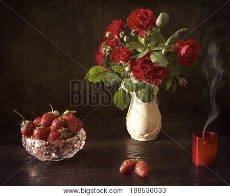 On the table strawberries and a vase with roses