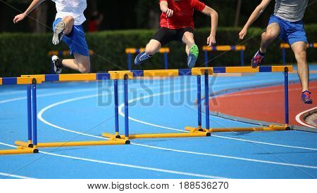 Three Young Athletes While Running Hurdles On The Running Track