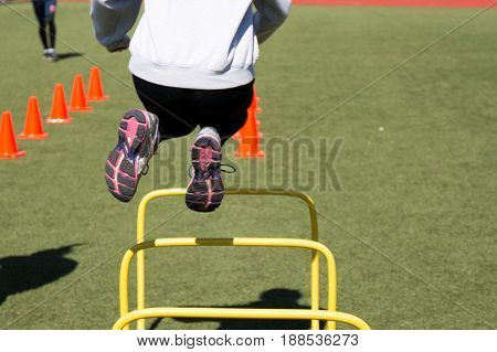 A track and fiells athlete jumps over a yellow hurdle while doing agility drills on a green turf