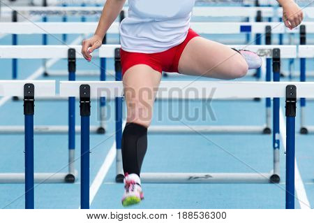 High school girl racing the hurdles at a track and field competition