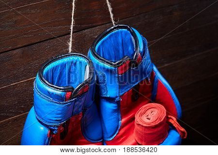 Blue and red boxing gloves and bandage on brown plank background. Horizontal photo of the boxing equipment against wooden wall. Boxing backgrounds and still-life. Concept of the sportive lifestyle.