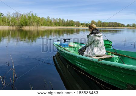 A woman is fishing while sitting in a boat. In the background, the banks of the reservoir are visible.
